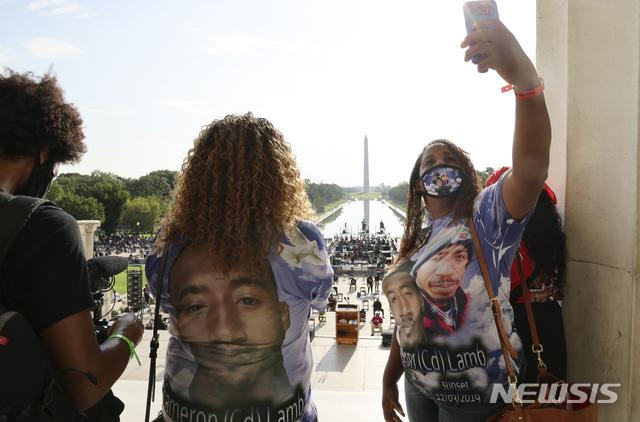 [캔사스시티( 미 미주리주)=AP/뉴시스] 지난해 8월 28일 캔사스시티 경찰의 총격과 폭력에 희생된 사람들의 사진을 들고 항의하는 가족들의 시위대. 2019년 사살당한 캐머런 램(26)의 어머니와 이모 등이 그의 어린 자녀들 4명을 대신해서 희생자의 사진을 몸에 두르고 워싱턴D.C. 시내에서 행진에 참가했다.