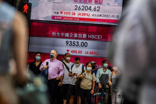 <YONHAP PHOTO-5823> 중국 기업 규제 공포에 폭락한 홍콩 증시      (홍콩 AFP=연합뉴스) 지난 7월 26일(현지 시각) 홍콩 최대 번화가인 센트럴 지역에서 행인들이 홍콩 증시의 대표 지수인 항셍지수의 종가를 알리는 전광판 앞에 서 있다. 주말인 지난 24일 중국 정부의 강력한 사교육 규제 조치가 공식 발표된 것을 계기로 시장 전반 규제 공포감이 확산하면서 이날 항셍지수는 전 거래일보다 4.09% 급락한 26,204.62까지 밀려 연중 최저 수준을 나타냈다. 중국 본토 상하이종합지수와 선전성분지수도 큰 폭으로 동반 하락했다.