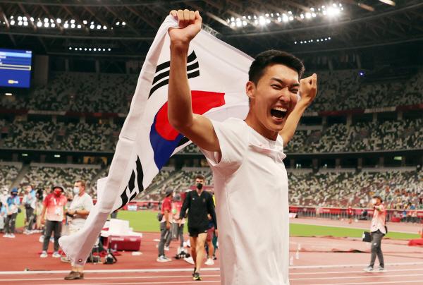 지난 1일 도쿄올림픽 남자 높이뛰기에서 2m35 한국신기록을 세우며 4위를 차지한 우상혁이 도쿄 올림픽스타디움에서 경기 종료 후 태극기를 펼치며 기뻐하고 있다. [사진 출처 = 연합뉴스]