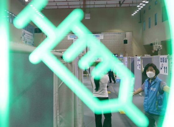 서울 동작구 예방접종센터가 설치된 사당종합체육관의 접종실에 주사기 모양의 조명이 들어와 있다.   국내 코로나19 1차 접종자수는 지난 3일 2000만명을 돌파했다. [연합뉴스]
