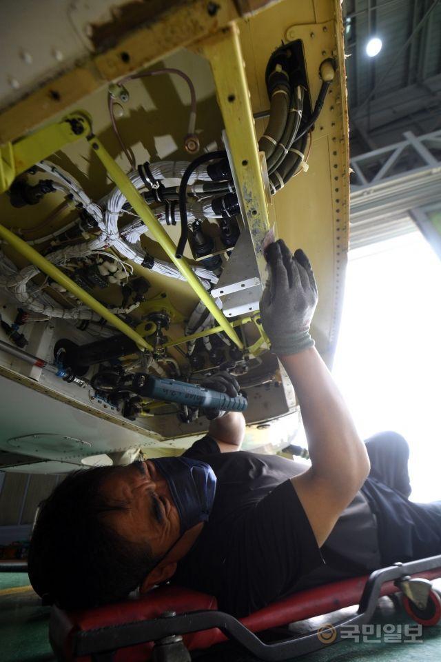 지난달 12일 해경 항공정비대 격납고에서 한 정비사가 헬기 바닥 부분에 염분과 녹을 긁어내고 있다.