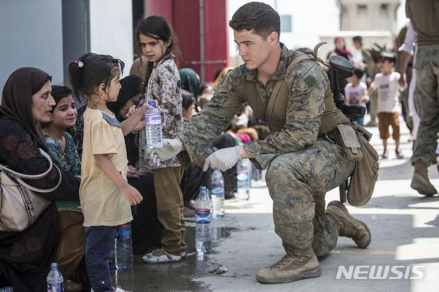 [카불=AP/뉴시스] 20일(현지시간) 아프가니스탄 카불의 하미드 카르자이 국제공항에서 한 미군 병사가 가족과 대피 대기 중인 한 어린이에게 생수를 건네고 있다. 조 바이든 미국 대통령은 탈레반이 장악한 아프간에서 모든 미국인을 귀환시킬 것과 미국을 지원한 모든 아프간인을 대피시킬 것을 재차 다짐했다. 2021.08.21.