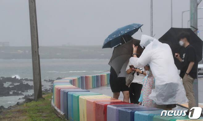 제14호 태풍 '찬투(CHANTHU)'가 북상 중인 14일 오전 제주시 용담해안도로에서 우산을 쓴 행인들이 발걸음을 옮기고 있다. 2021.9.14/뉴스1 © News1 오현지 기자