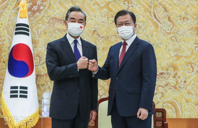 문재인(오른쪽) 대통령이 15일 청와대에서 왕이 중국 외교부장을 접견하기 전 주먹 인사를 하고 있다. 왕태석 선임기자