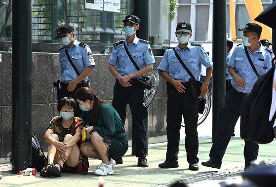15일 중국 광둥성 선전시의 헝다그룹 본사 앞에서 '돈을 돌려달라'면서 투자자들이 시위를 하고 있다. 그 앞을 [AFP=연합뉴스]