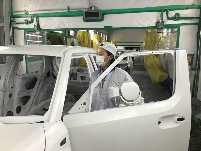 노사 상생형 '광주형 일자리'를 내세운 광주글로벌모터스(GGM) 도장부 생산라인에서 직원이 도장된 차량을 살펴보고 있다./광주글로벌모터스