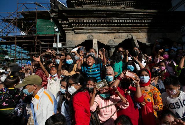 네팔 주민들이 옌야 축제의 일환으로 열리는 쿠마리의 연례 행차를 관람하기 위해 19일 카트만두 시내 거리에 모여 있다. 카트만두=AP 연합뉴스