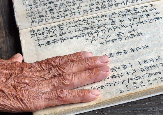 화사별서 조한승 옹이 어릴 적 손수 적었다는 서책을 펼쳐보이며 읽고 있다.