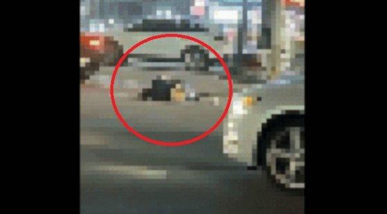 지난 5월7일 충남 서산시 갈상동 사거리에서 도로 위에 누워 있는 여성을 승용차가 밟고 지나가는 모습. [온라인 커뮤니티 '보배드림' 캡처]