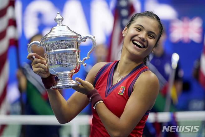 [뉴욕=AP/뉴시스] 엠마 라두카누(150위·영국)가 11일(현지시간) 미국 뉴욕의 아서애시스타디움에서 열린 US오픈 테니스 대회 여자 단식 결승전에서 레일라 페르난데스(73위·캐나다)를 물리치고 우승, 트로피를 들고 활짝 웃고 있다. 10대 선수끼리 맞붙은 결승전에서 라두카누는 페르난데스를 세트스코어 2-0(6-4 6-3)으로 꺾고 10경기 무실세트 우승을 차지했다. 2021.09.12.