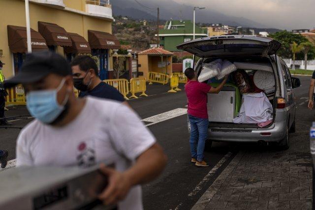 22일 야노스 마을 주민들이 화산 폭발로 분출하고 있는 용암을 피해 대피하면서 집에서 가지고 나온 소지품을 챙기고 있다. AP=뉴시스