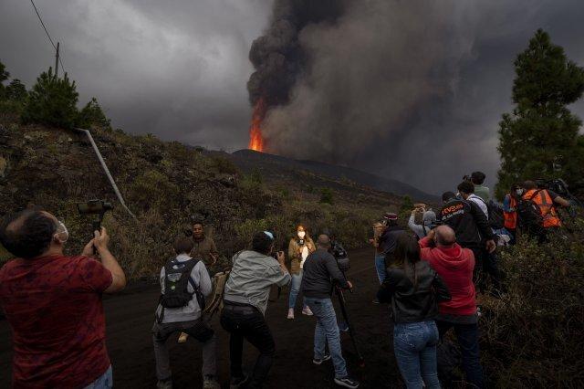 22일 취재진들이 화산이 폭발한 인근 마을에서 현장 상황을 보도하고 있다. AP=뉴시스