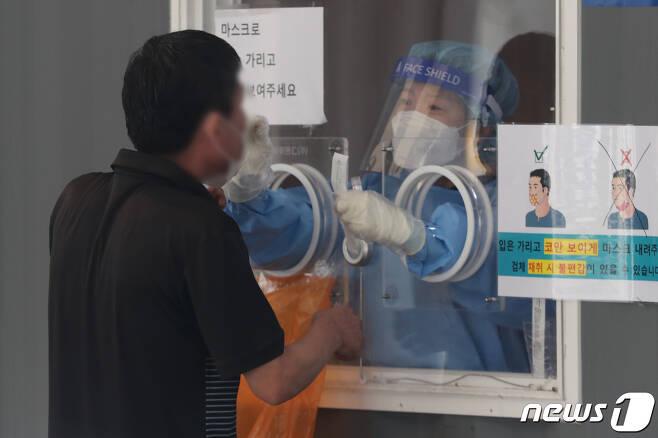 25일 오전 서울 서울역광장에 마련된 중구 선별검사소에서 한 시민이 코로나19 검체 검사를 받고 있다. 이날 코로나19 신규 확진자는 3273명을 기록해 역대 최다를 기록했다. 2021.9.25/뉴스1 © News1 박세연 기자