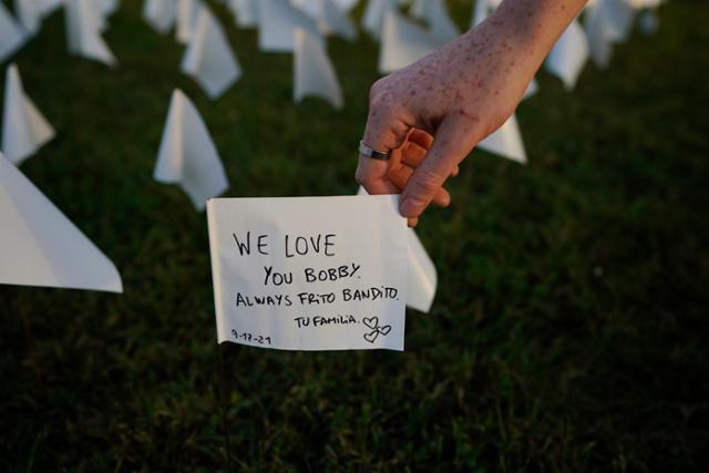 17일 미국 워싱턴 내셔널 몰을 찾은 시민이 하얀 깃발에 적힌 코로나19 희생자 추모 메시지를 보고 있다. 워싱턴=AP 연합뉴스