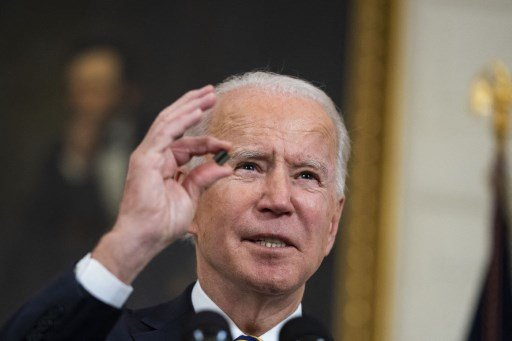 조 바이든 미국 대통령이 4월 12일(현지시간) 백악관 루즈벨트룸에서 반도체 업계 대표들과 화상 회의를 진행하는 도중 반도체 칩을 들어보이고 있다./사진=AFP
