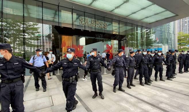 파산 위기에 몰린 중국의 대형 민영 부동산 재벌기업인 헝다(恒大·에버그란데)그룹의 선전 본사 사옥 주변에서 경비원들이 손을 맞잡고 투자금 반환을 요구하는 시위대의 접근을 막고 있다.