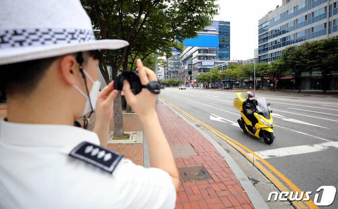 경찰이 28일 인천시 연수구 송도동에서 캠코더로 교통법규 위반한 이륜차를 단속하고 있다.2021.9.28/뉴스1 © News1 정진욱 기자