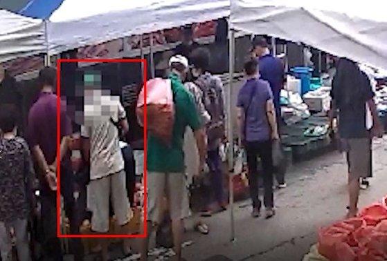 지난달 24일 대전시 유성시장에서 한 남성(붉은색 사각형)이 물건을 사는 여성의 가방에서 지갑을 훔치고 있다. [사진 대전경찰청]