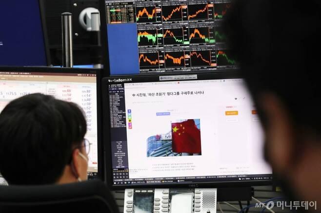 지난달 23일 오후 서울 중구 하나은행 딜링룸에서 관계자가 헝다그룹 관련 기사를 보고 있다. /사진=김휘선 기자 hwijpg@